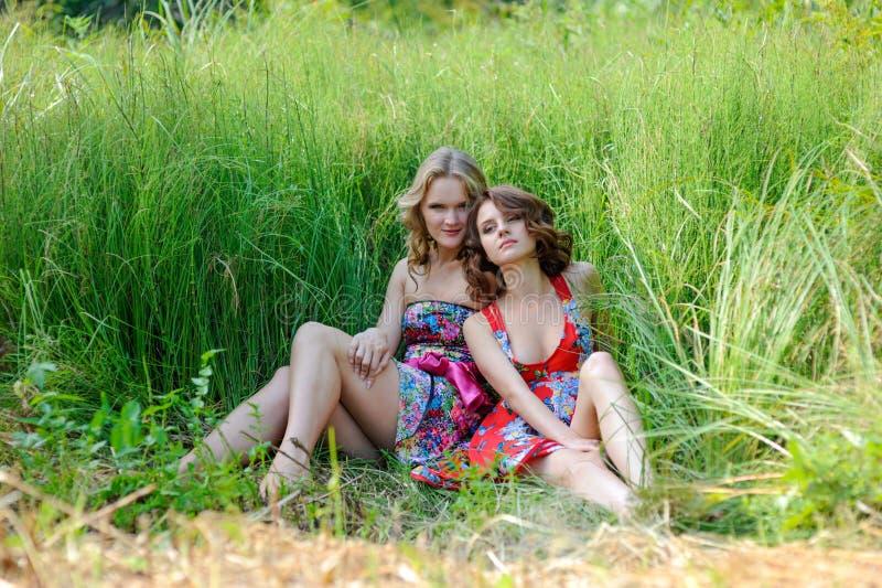 两个年轻白肤金发的女孩和棕色毛发的妇女摆在夏天的明亮的礼服的在高草停放 图库摄影