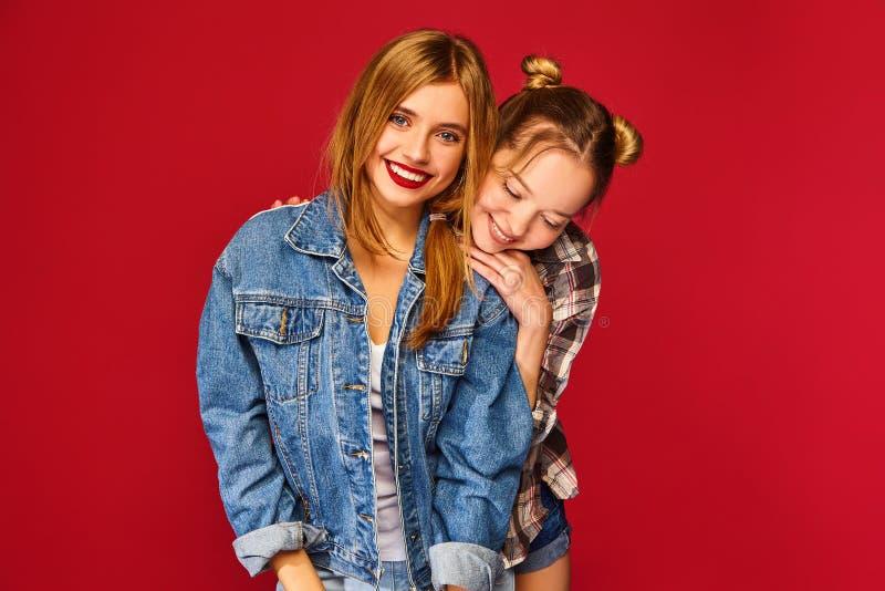 两个年轻美丽的白肤金发的微笑的行家女孩 免版税库存照片