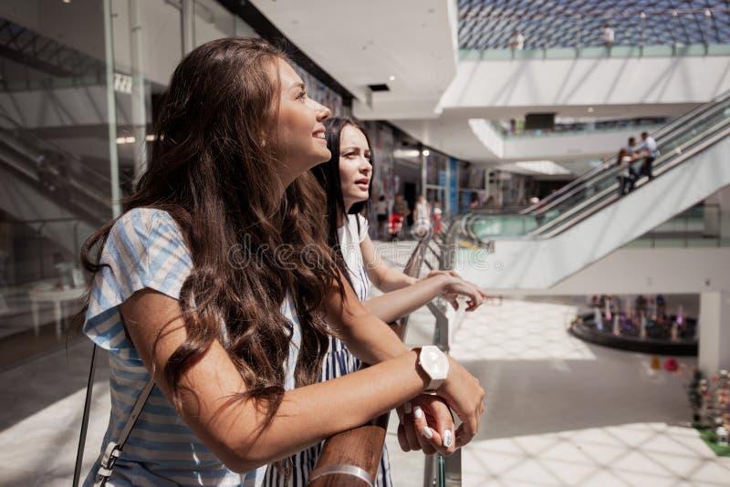 两个年轻逗人喜爱的稀薄的深色头发的女孩,立场紧挨着在一个现代购物中心 免版税库存图片