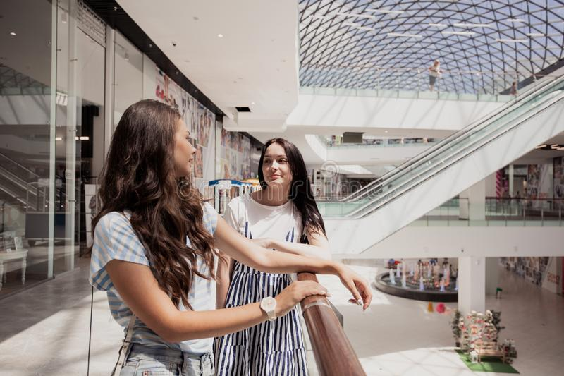 两个年轻逗人喜爱的稀薄的深色头发的女孩,立场紧挨着在一个现代购物中心 免版税库存照片