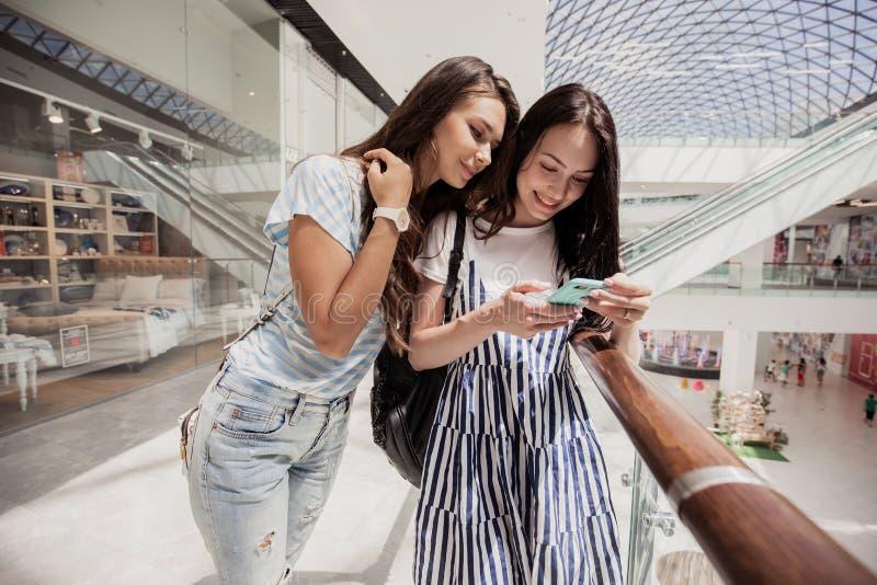 两个年轻逗人喜爱的稀薄的深色头发的女孩,立场紧挨着在一个现代购物中心 图库摄影
