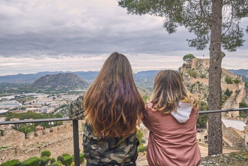 两个年轻金发和棕色毛发的十几岁的女孩在巴伦西亚,西班牙观察在克萨蒂瓦城堡里面的风景 免版税库存图片