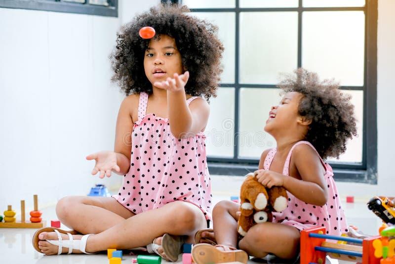两个年轻非洲女孩一起使用更旧的投掷与活动的一些玩具和女孩神色乐趣 库存图片