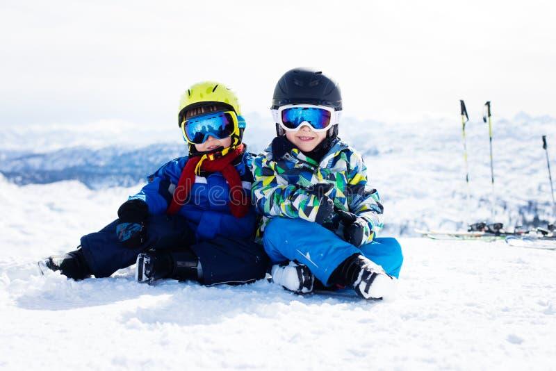 两个幼儿,兄弟姐妹兄弟,滑雪在奥地利mounta 免版税库存照片