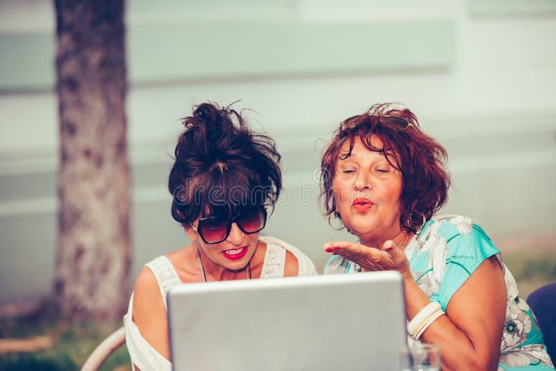 两个开心的高级女性坐在一家咖啡馆里,用笔记本电脑在视频通话中在网上发吻 免版税库存图片