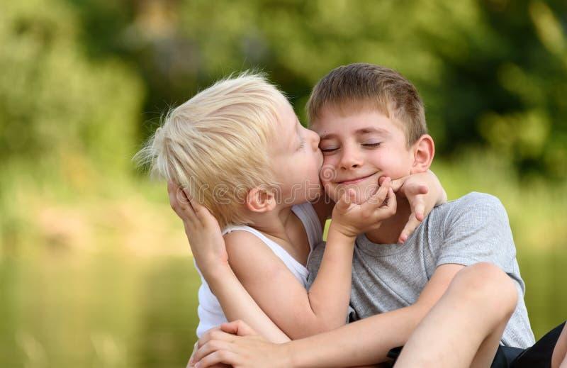 两个弟弟坐户外 一个人亲吻其他在面颊 在距离的被弄脏的绿色树 概念  免版税库存照片
