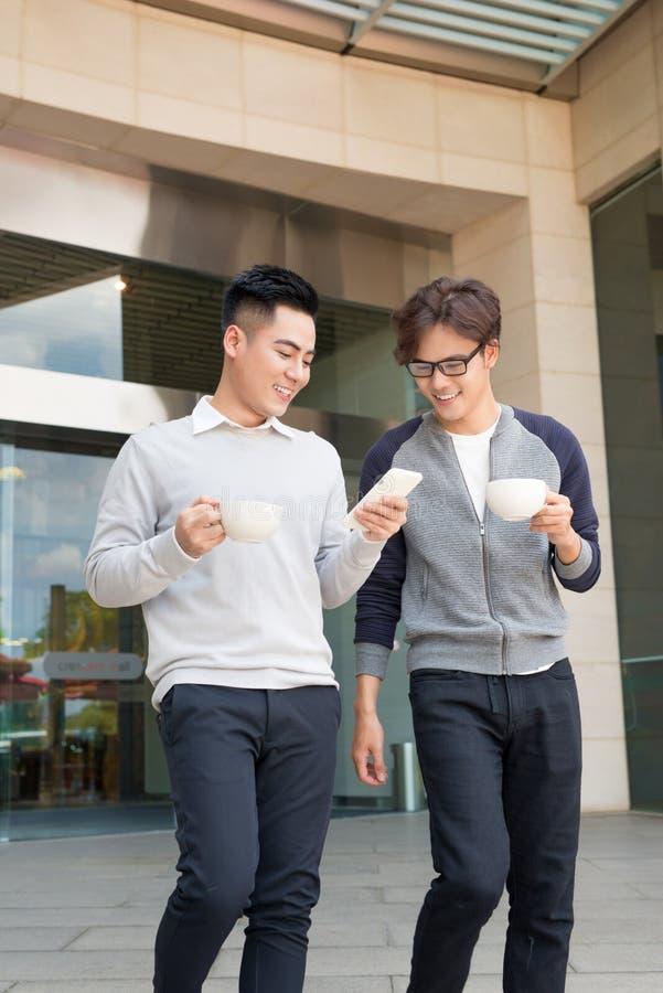两个微笑的商人走和谈话在城市 免版税库存照片