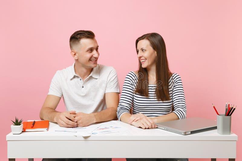 两个微笑的女商人人同事工作在有当代膝上型计算机的白色书桌坐粉红彩笔背景 免版税库存图片