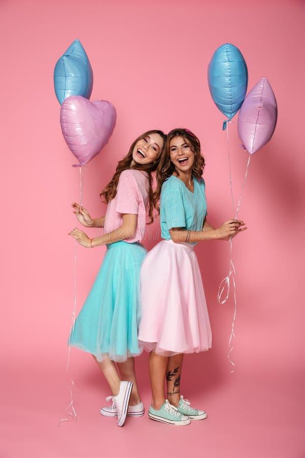 两个微笑的女孩在明亮的五颜六色的衣裳穿戴了 图库摄影
