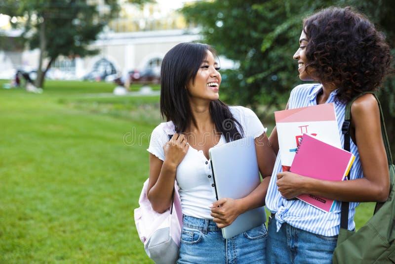 两个微笑的少女女学生身分户外 免版税图库摄影