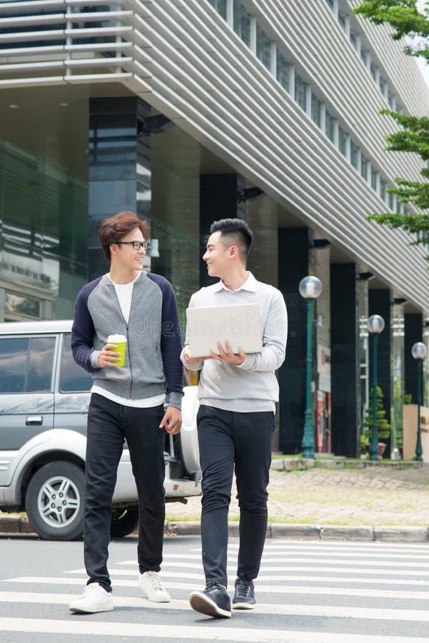 两个微笑的年轻商人走和谈话在城市 库存图片
