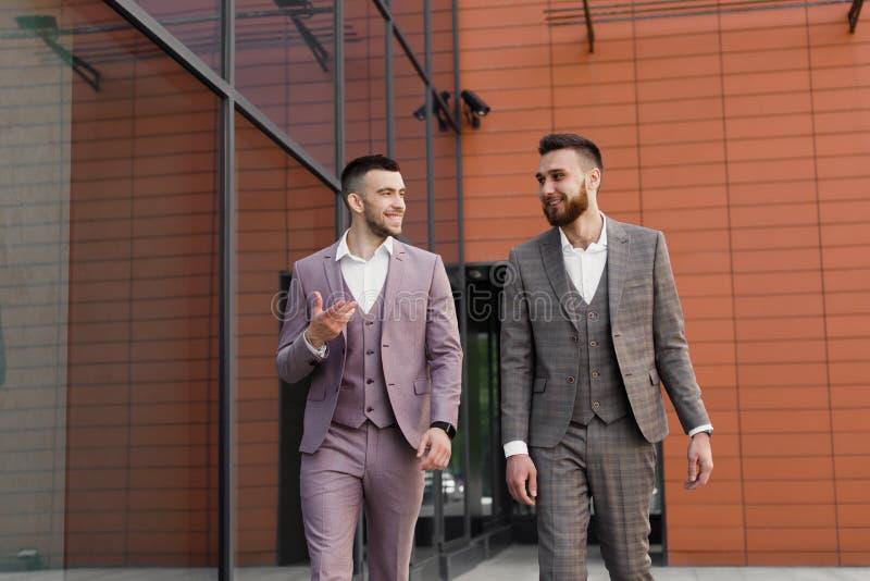 两个微笑的年轻商人走和谈话在城市 免版税图库摄影