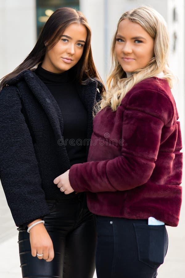 两个微笑的美丽的年轻女人朋友画象在城市 库存图片