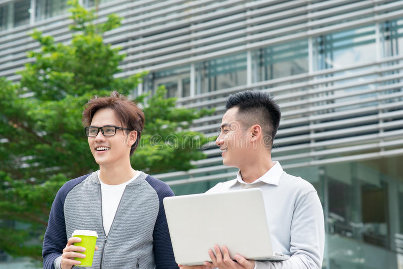 两个微笑的年轻商人走和谈话在城市 库存照片