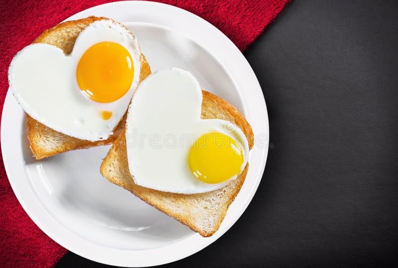 两个心形的煎蛋和油煎的多士 库存照片