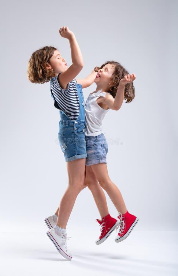 两个快乐活动过度年轻姐妹跳跃 免版税图库摄影