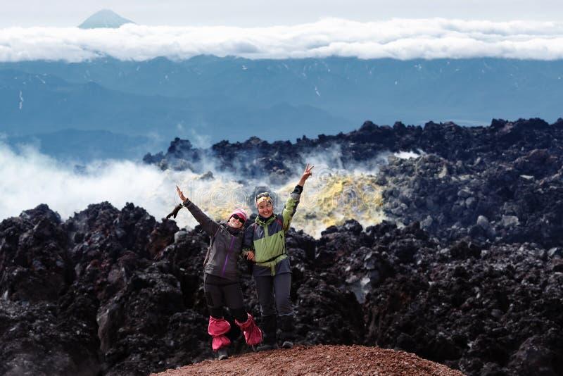 两个快乐的女朋友在活火山火山口站立  免版税库存照片