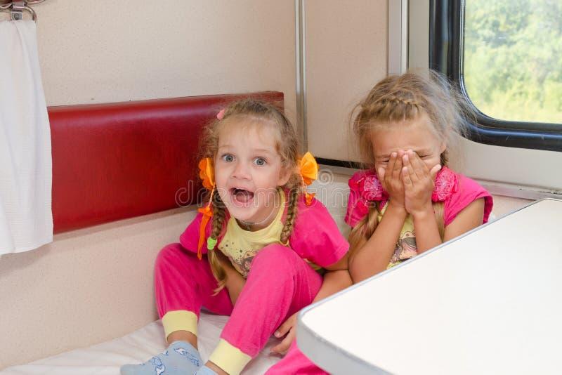 两个快乐的小女孩坐在更低的第二等的地方汽车的火车在同样睡衣 免版税图库摄影