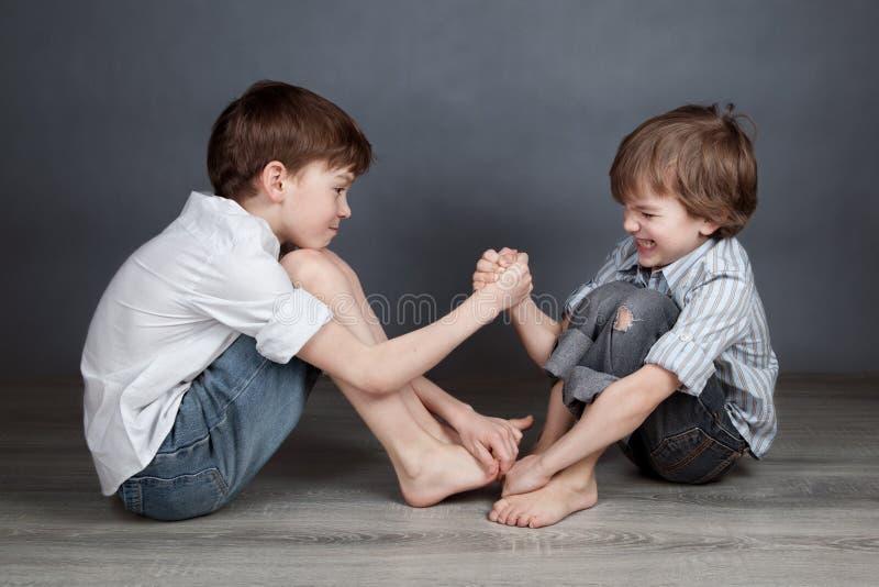 两个愉快的兄弟画象agray背景的 库存图片