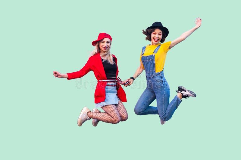两个愉快的叫喊的时髦的行家女孩充分的腿身体尺寸画象时装的是跳跃悬而未决和 免版税库存照片