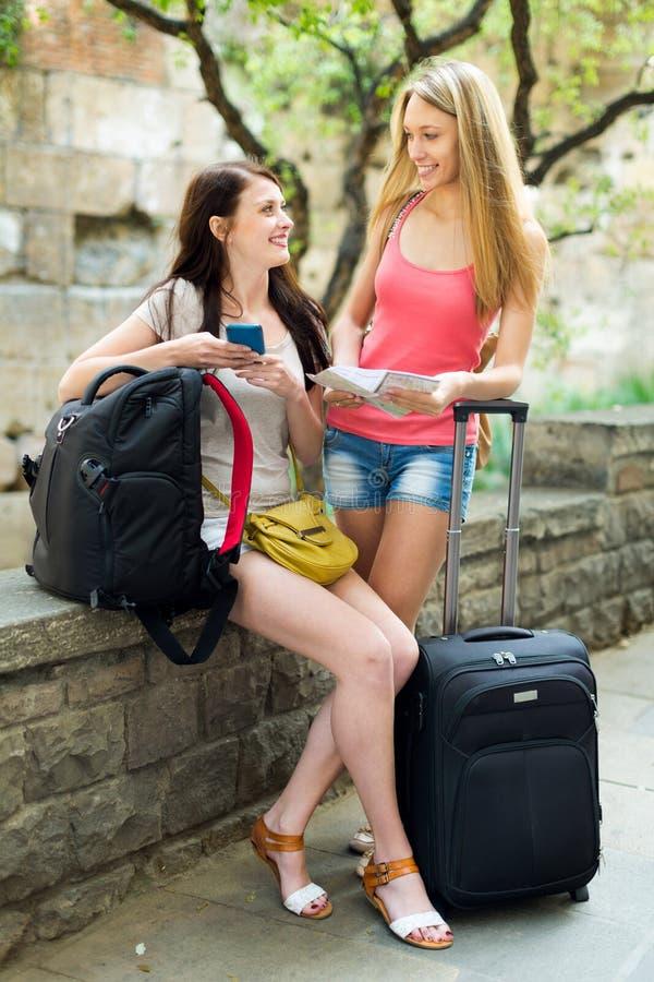 两个愉快的女孩在度假与行李的 免版税库存图片
