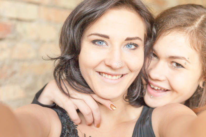 两个愉快的女孩在照相机或手机做selfie 库存图片