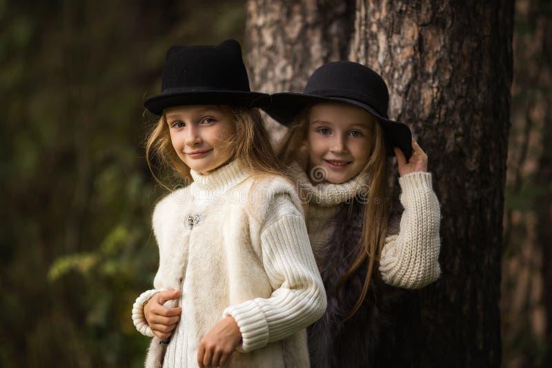 两个愉快的女孩平等地打扮:在毛皮背心和帽子在森林小女朋友在公园 库存照片