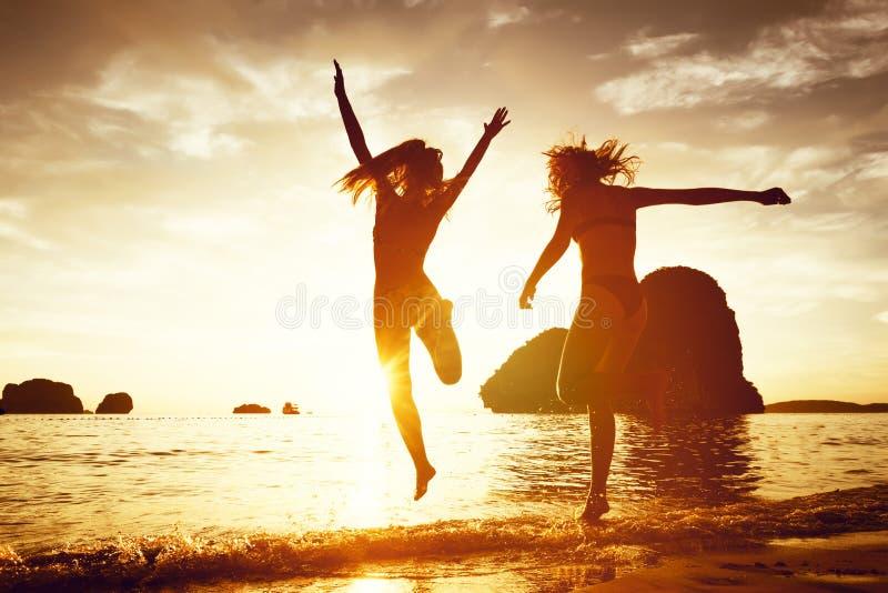 两个愉快的女孩日落海滩奔跑跃迁 库存图片