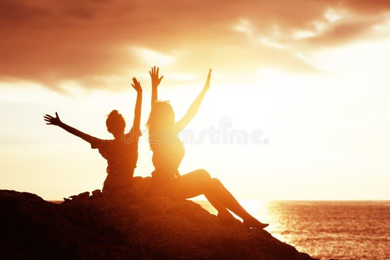 两个愉快的女孩用反对日落海的被举的手 免版税库存照片