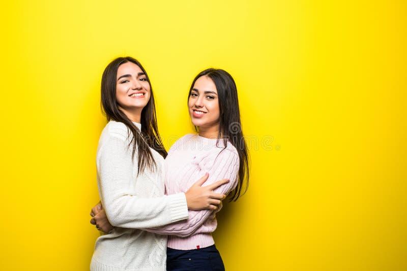 两个愉快的女孩画象在毛线衣拥抱穿戴了被隔绝在黄色背景 免版税图库摄影