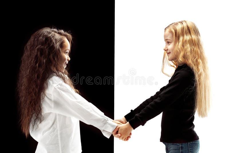两个愉快的女孩画象白色和黑背景的 免版税库存照片