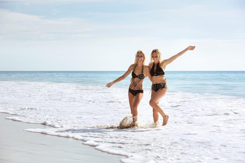 两个愉快的女孩获得乐趣在海海滩 图库摄影