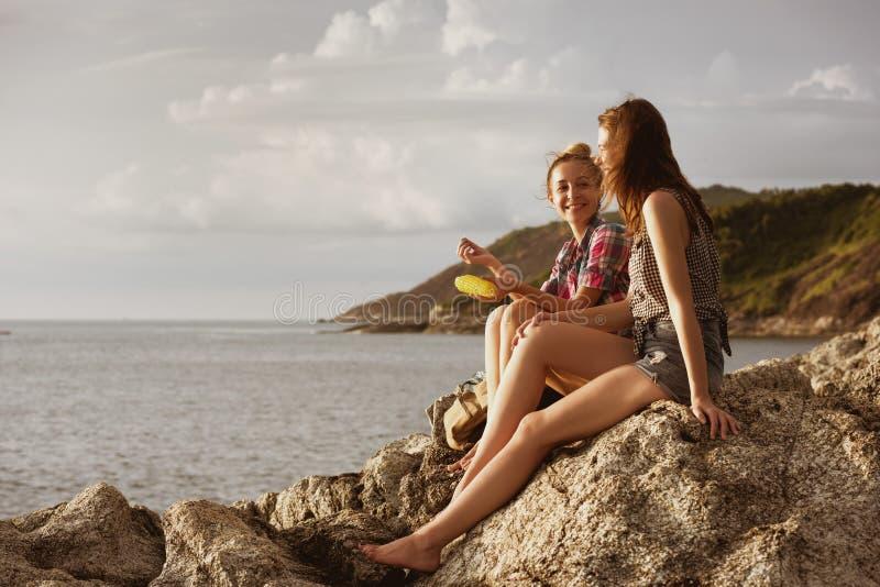 两个愉快的女孩讲话在日落海滩 库存照片