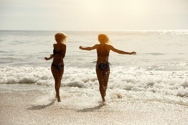 两个愉快的女孩跑热带海海滩 免版税库存照片