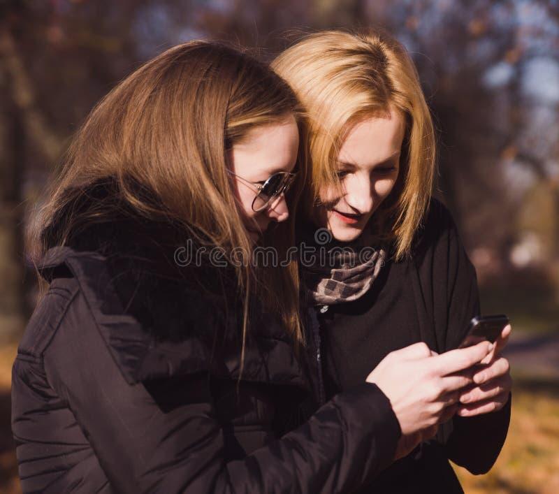 两个愉快的妇女朋友在聪明的电话ou中的分享社会媒介 库存图片