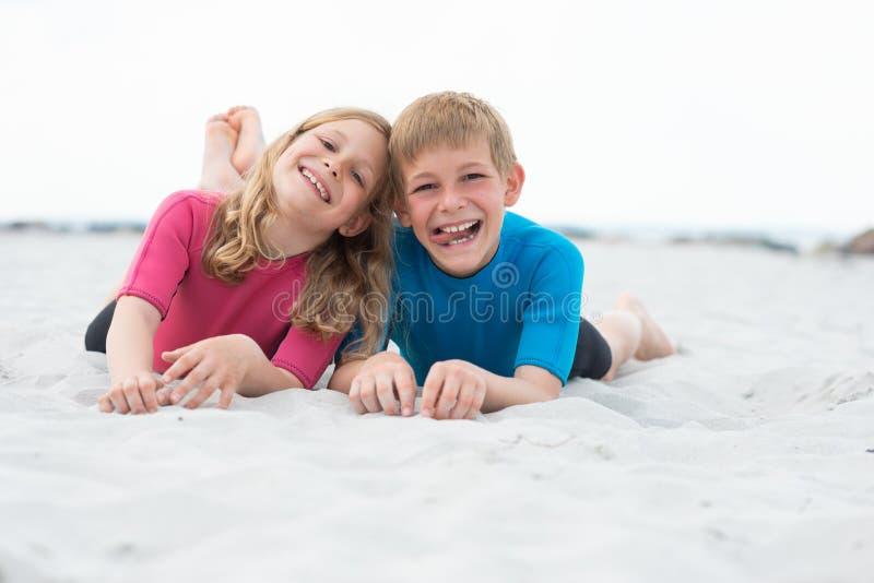 两个愉快的孩子画象使用在与沙子的海滩的氯丁胶泳装的 免版税库存照片