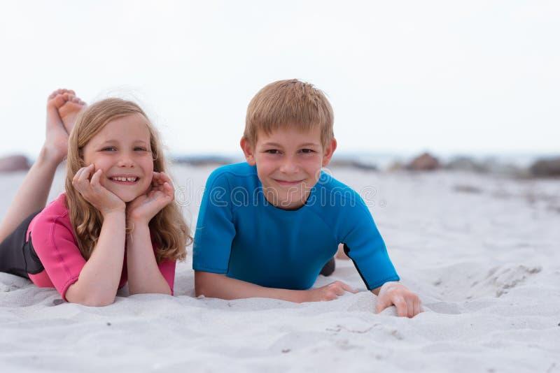 两个愉快的孩子画象使用在与沙子的海滩的氯丁胶泳装的 免版税图库摄影