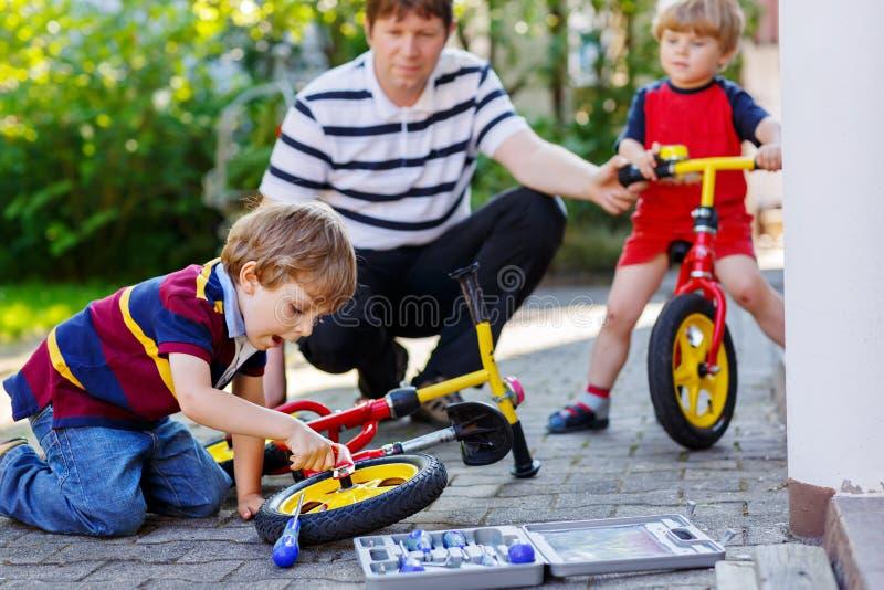 两个愉快的小孩男孩和父亲修理在自行车和平衡自行车变速轮的链子  库存图片