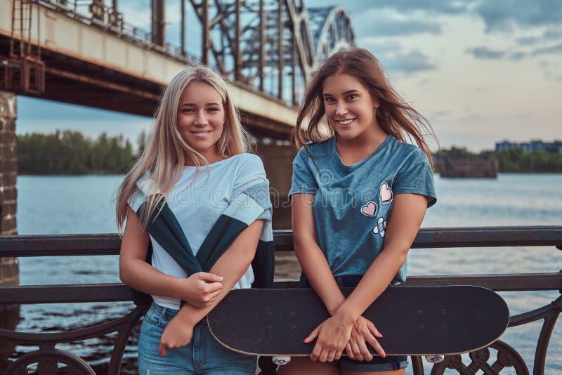 两个愉快的年轻行家女孩举行滑板和倾斜在老桥梁的背景的一根栏杆 库存图片