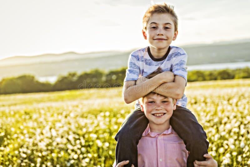 两个愉快的快乐的兄弟画象日落的,室外 库存图片