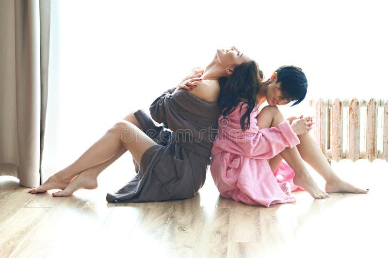 两个愉快的性感的少妇,女朋友,晨衣的,坐与他们的后面的地板 非常规的夫妇 库存照片