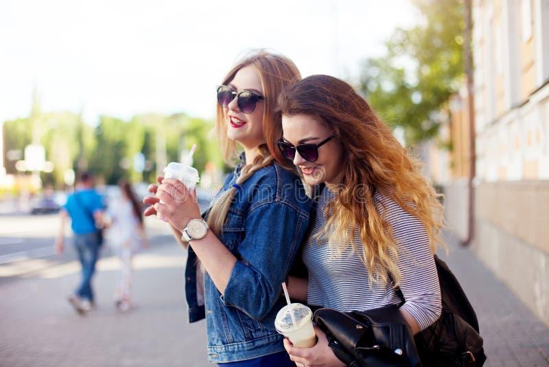 两个愉快的朋友女孩生活方式画象走笑谈话并且喝戴时髦明亮的衣裳和太阳镜的柠檬水 女孩 库存照片