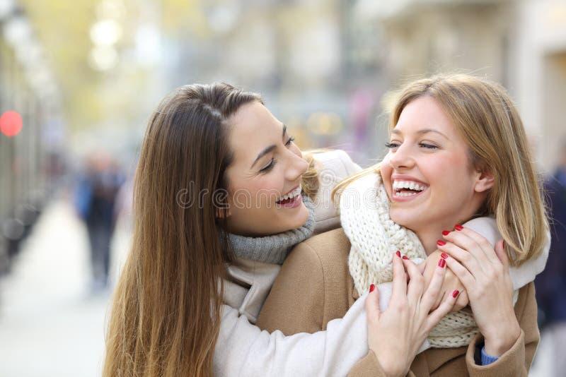 两个愉快的朋友耍笑在街道上在冬天 免版税库存图片