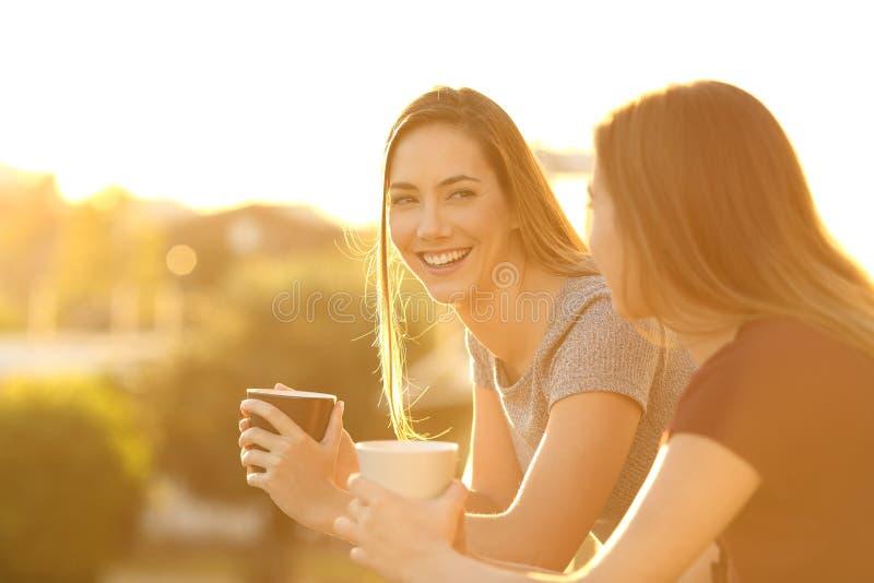 两个愉快的朋友谈话在阳台上在日落 免版税图库摄影