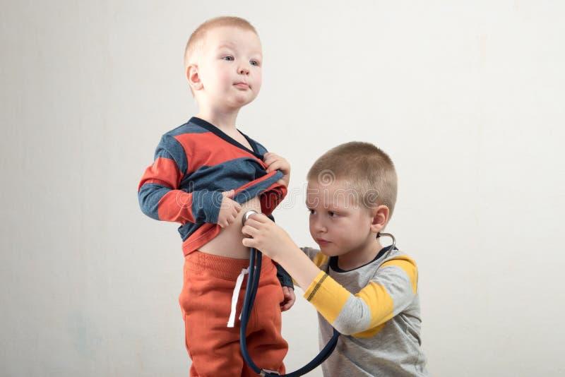 两个愉快的男孩在家使用与听诊器 家庭医生 库存照片