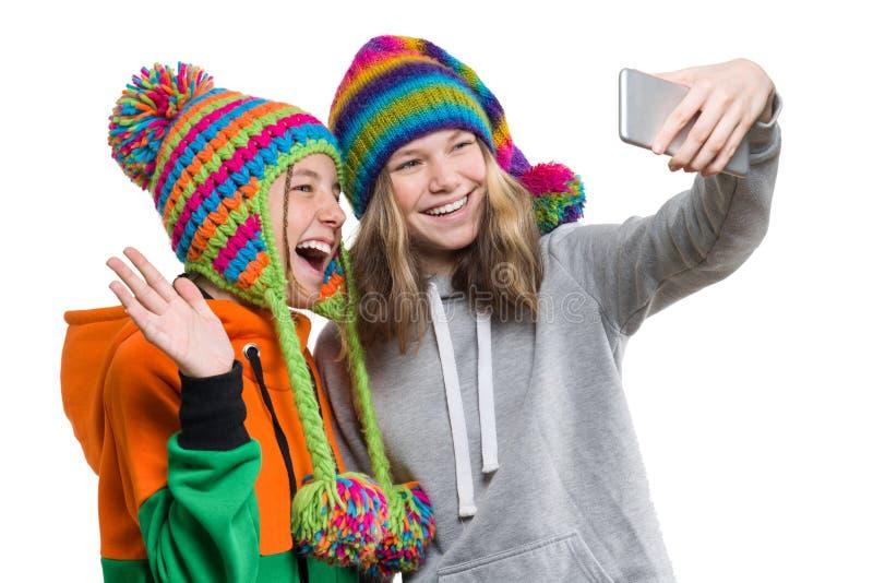 两个愉快的美丽的少年女朋友冬天画象获得被编织的帽子的与手机的乐趣,采取selfie,隔绝了o 免版税图库摄影