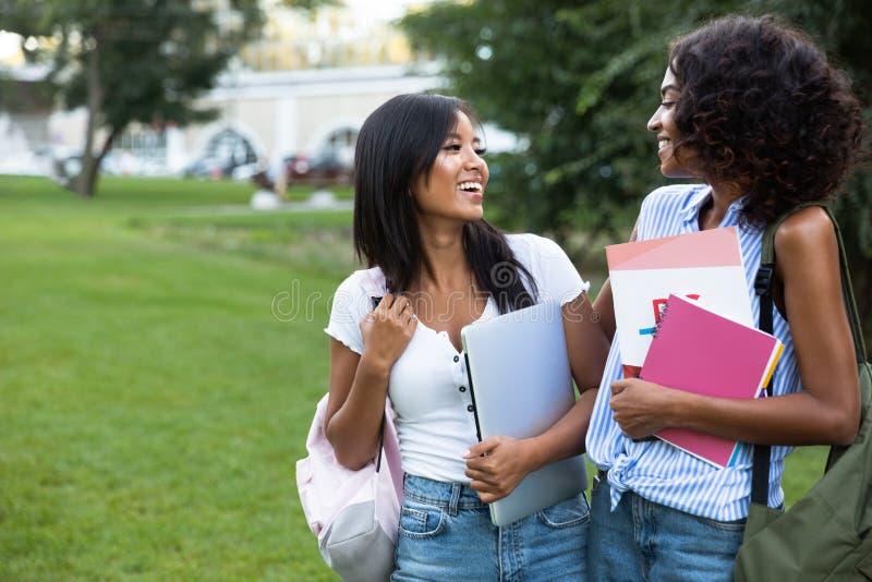 两个户外快乐的少女女学生身分 库存照片