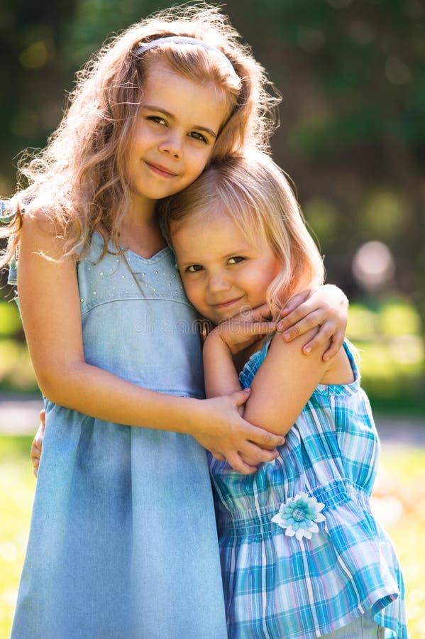 两个拥抱的逗人喜爱的小女孩室外画象  库存图片
