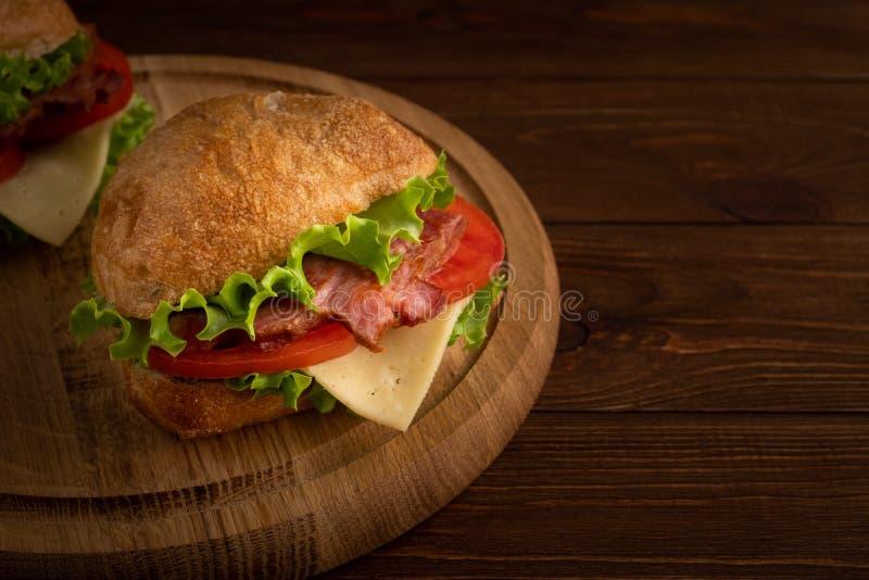两个新鲜的三明治用火腿,乳酪,烟肉,蕃茄,在黑暗的木背景的莴苣 免版税库存照片
