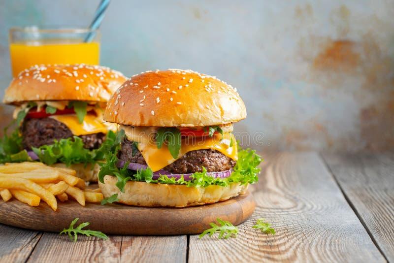 两个新鲜的自创汉堡用油煎的土豆和橙汁过去在一张木桌上 复制空间 免版税库存图片
